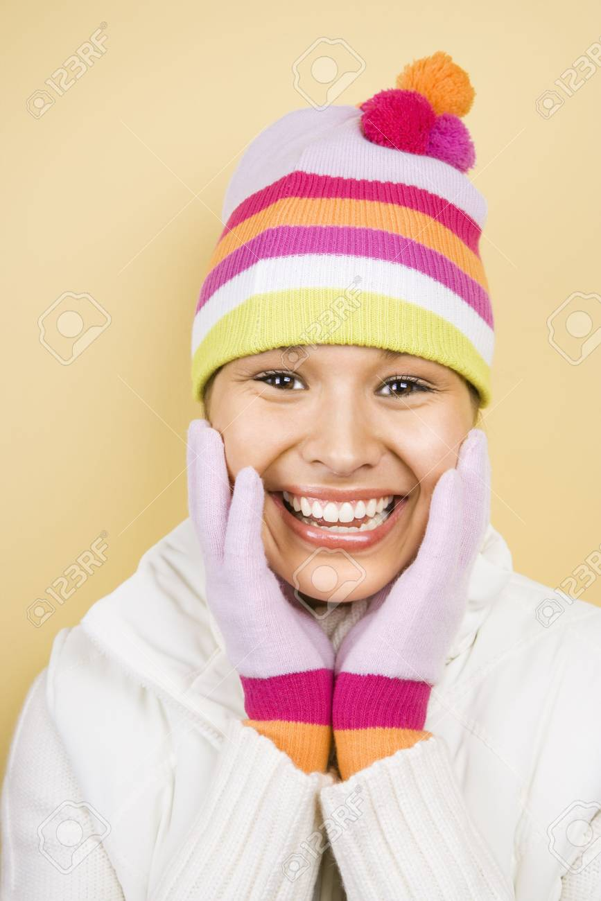 Young adult Caucasian woman wearing winter hat and gloves with hands to face smiling at viewer. Stock Photo - 1841839