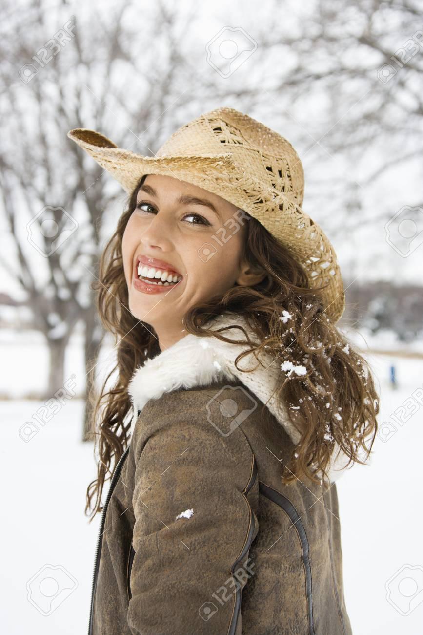 ... sombrero vaquero de paja. Caucásicos de mujeres adultas jóvenes al aire  libre en la nieve en el espectador sonriendo llevar c0b9e2bcbe8