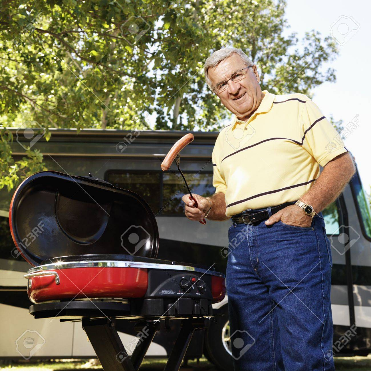 Senior adult man grilling hotdogs with RV in background. Stock Photo - 1850212