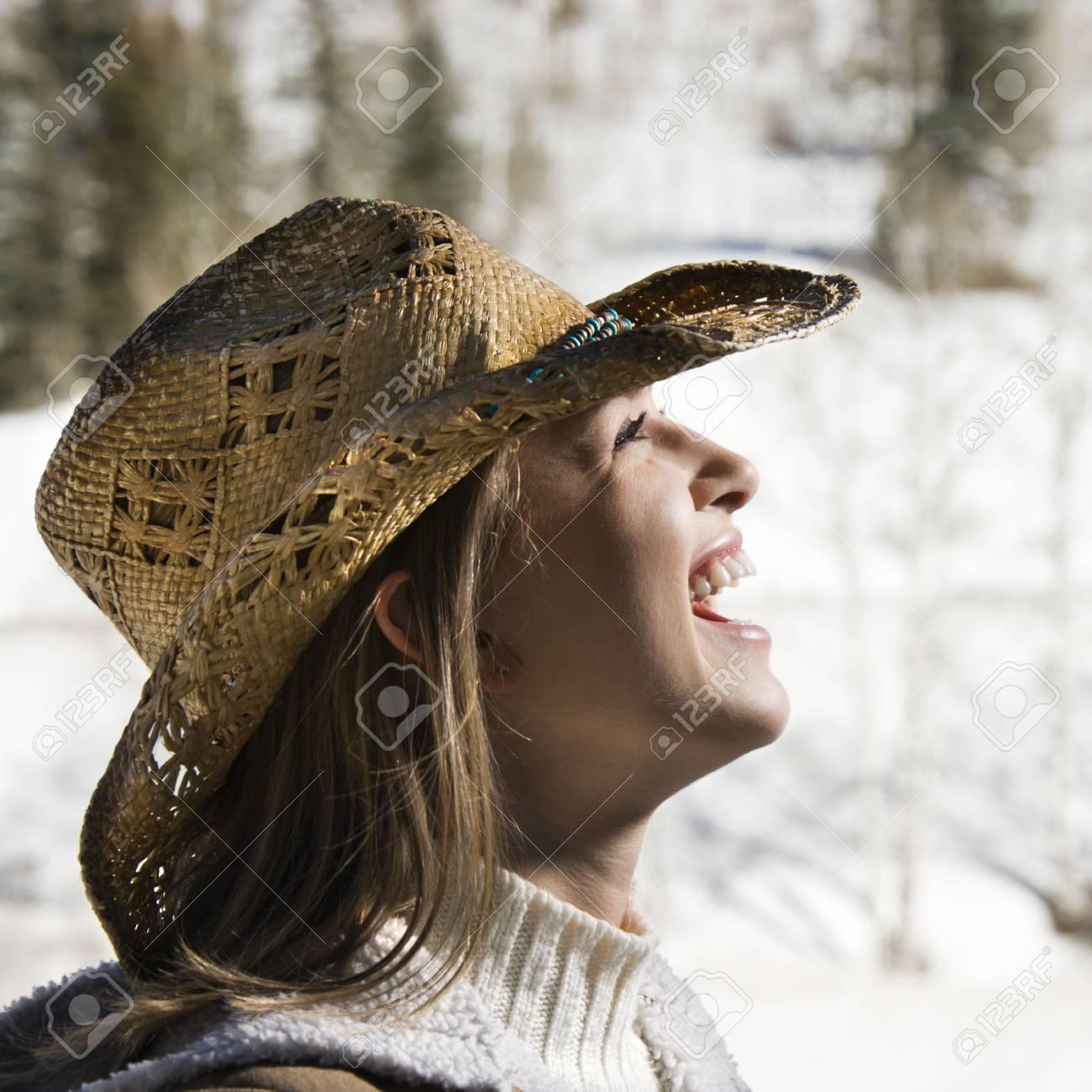 1e7a9825b6 Foto de archivo - Joven mujer de raza caucásica risa usar sombrero vaquero  al aire libre en invierno.