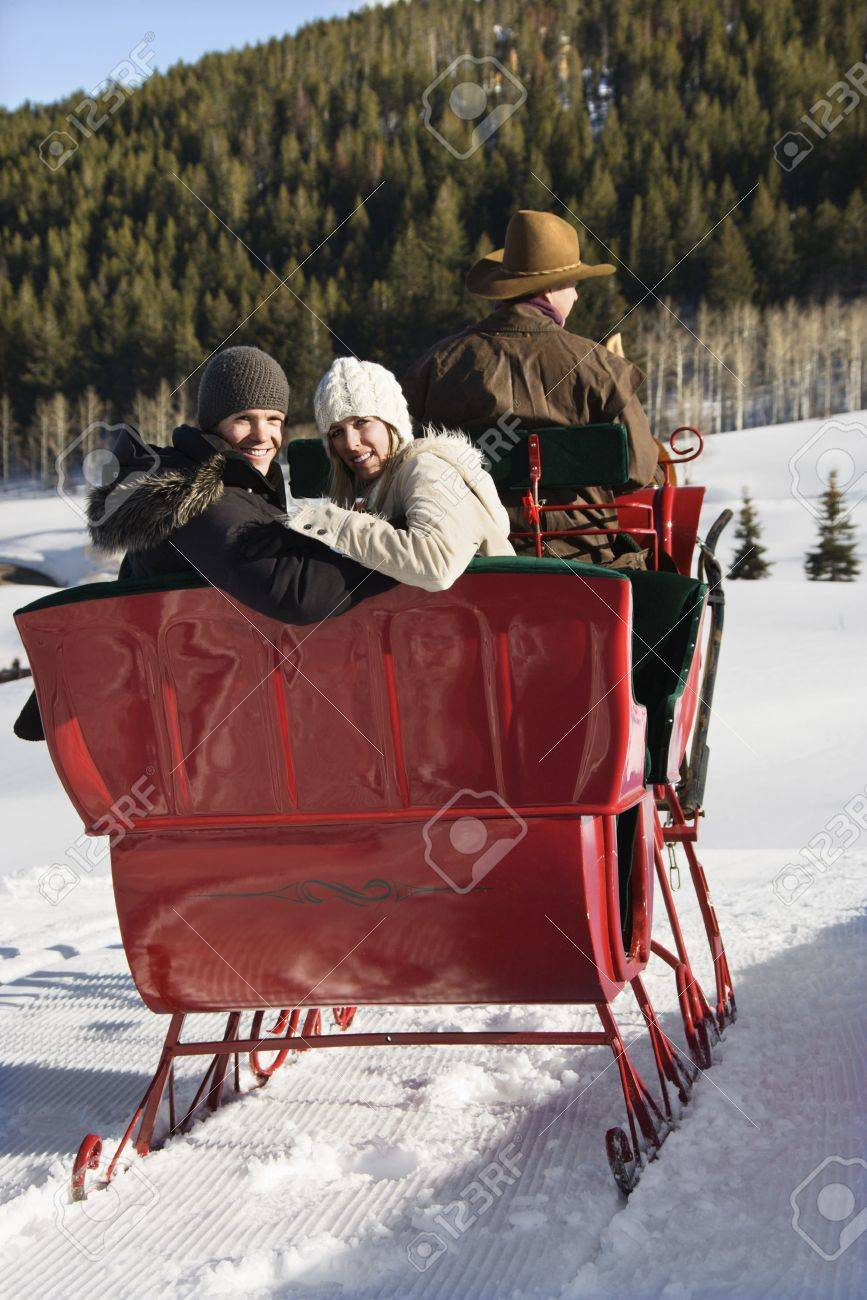 Rear view of man driving horse drawn sleigh with young couple looking back at viewer. Stock Photo - 1859046