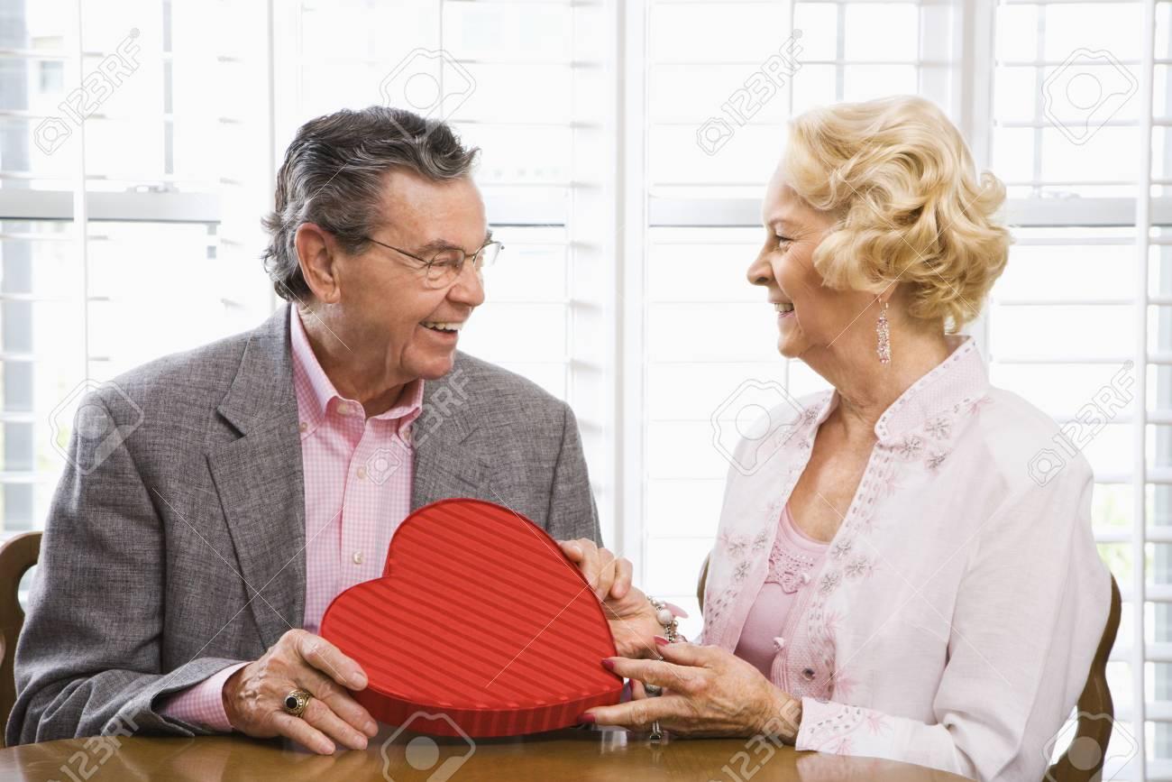 Mature Caucasian man giving Valentine heart box to mature Caucasian woman. Stock Photo - 1859056