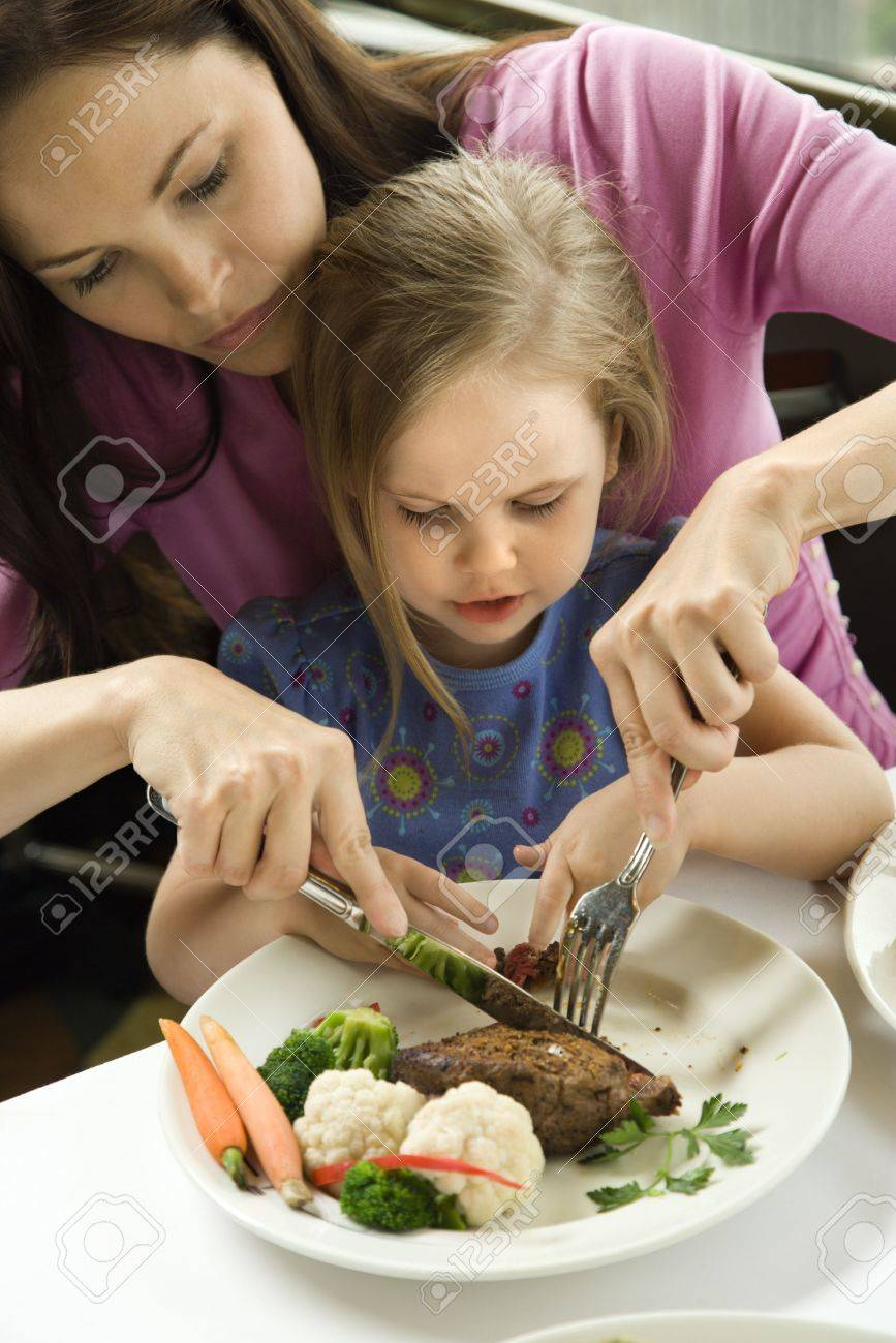 Caucasian mother helping cut meat for her daughter. Stock Photo - 1869027