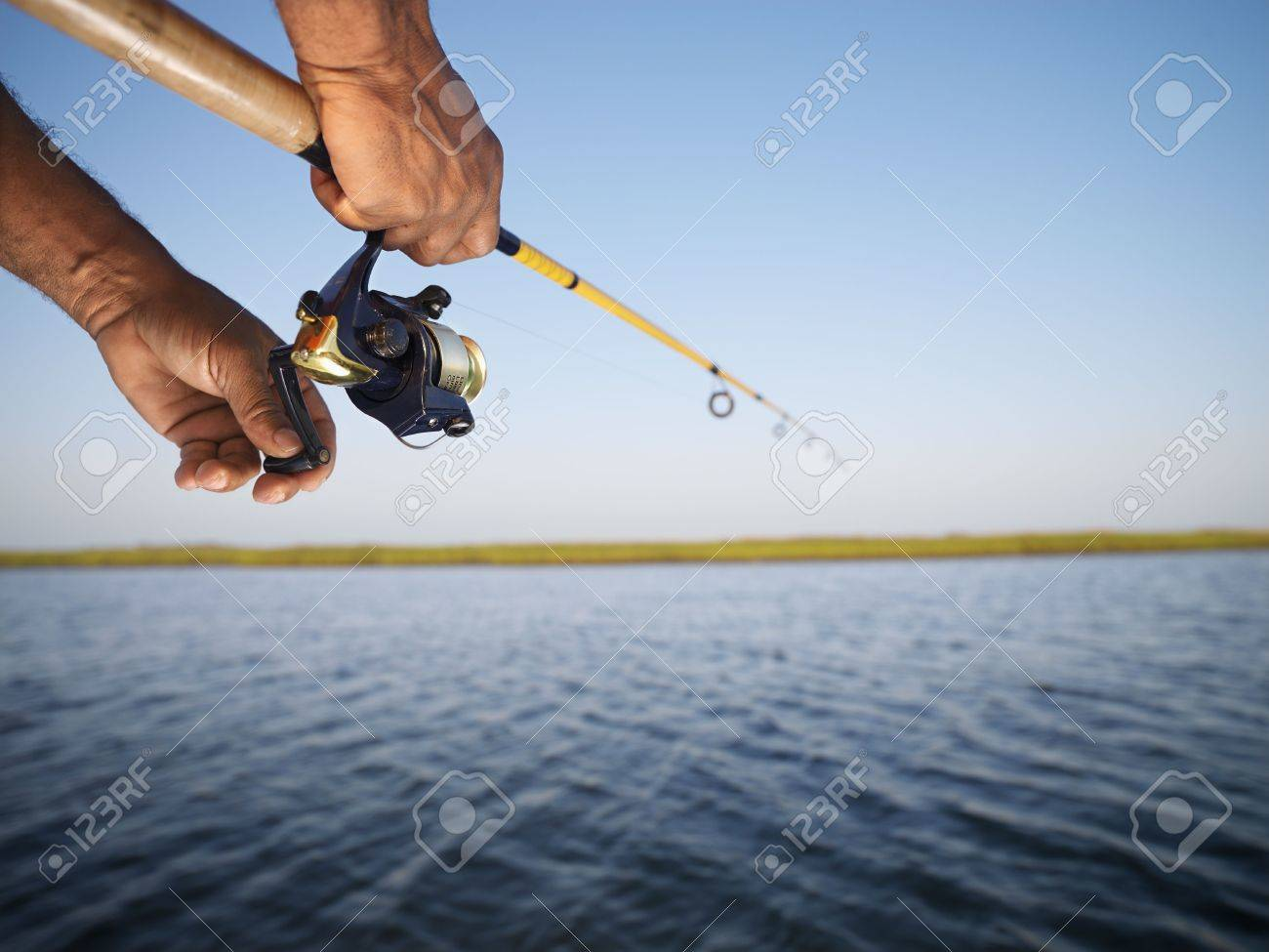 African-American male hand holding fishing rod and reeling the other hand. Stock Photo - 1868894