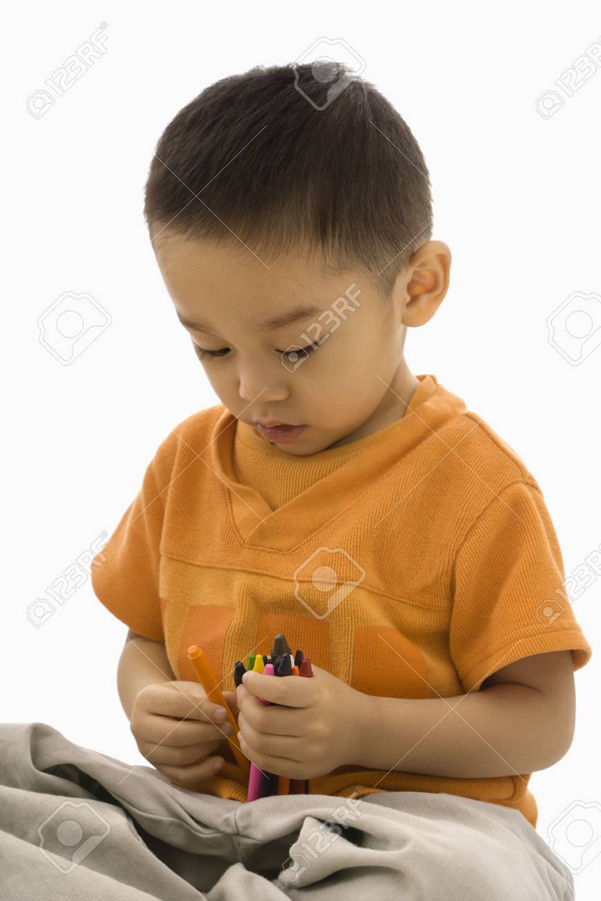 Asian boy sitting with handful of crayons. Stock Photo - 1868990