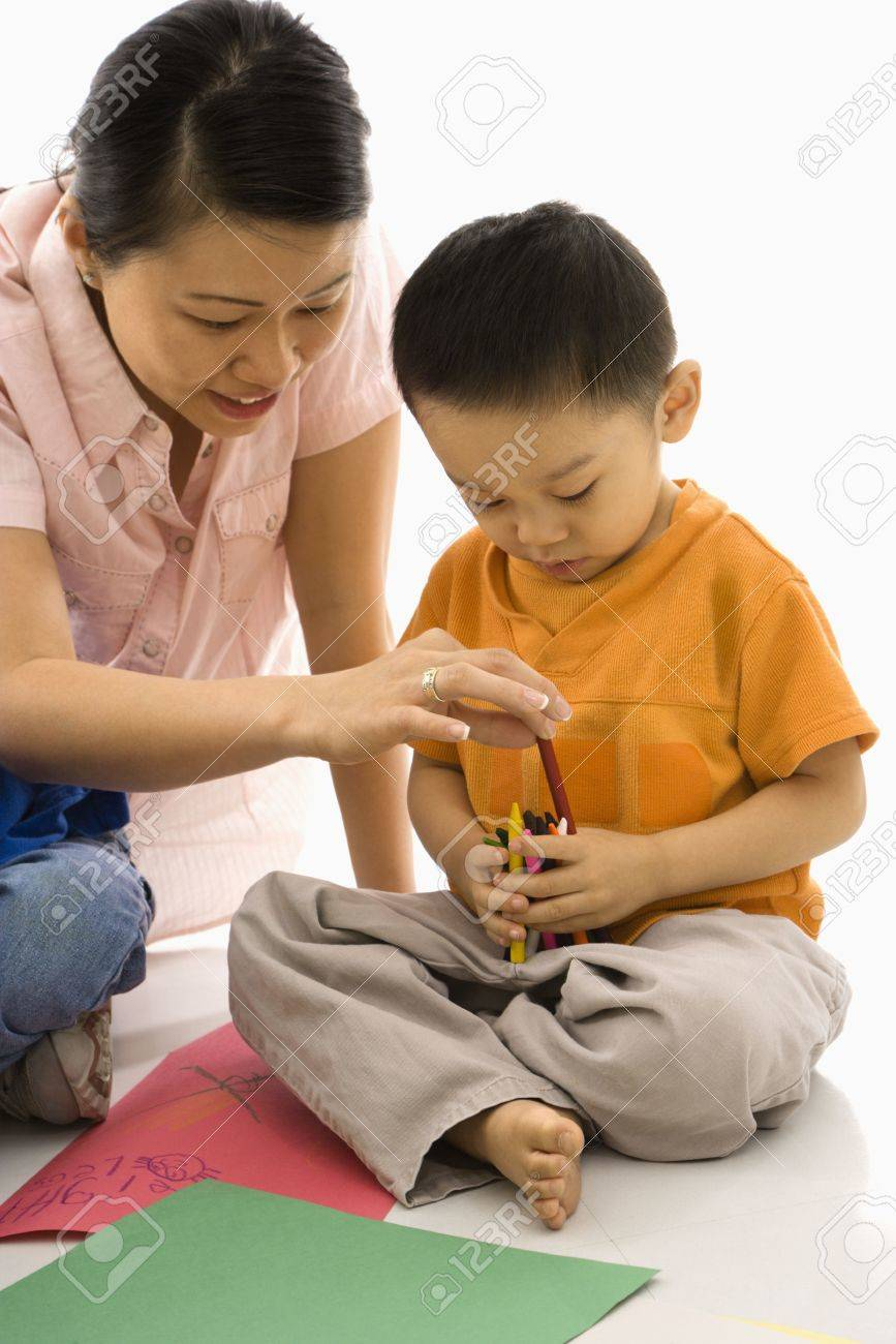 Asian Boy And Mother Coloring With Crayons Stock Photo
