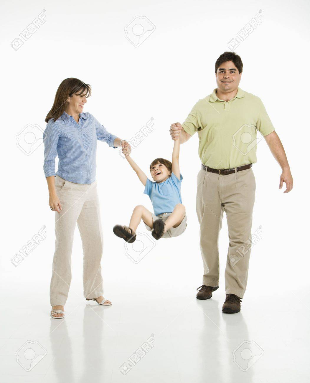 Hispanic mother and father swinging son against white background. Stock Photo - 1874345