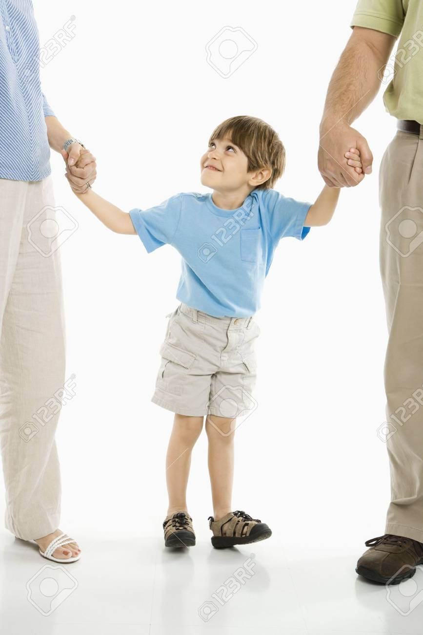 Boy holding hands with parents standing against white background. Stock Photo - 1874375