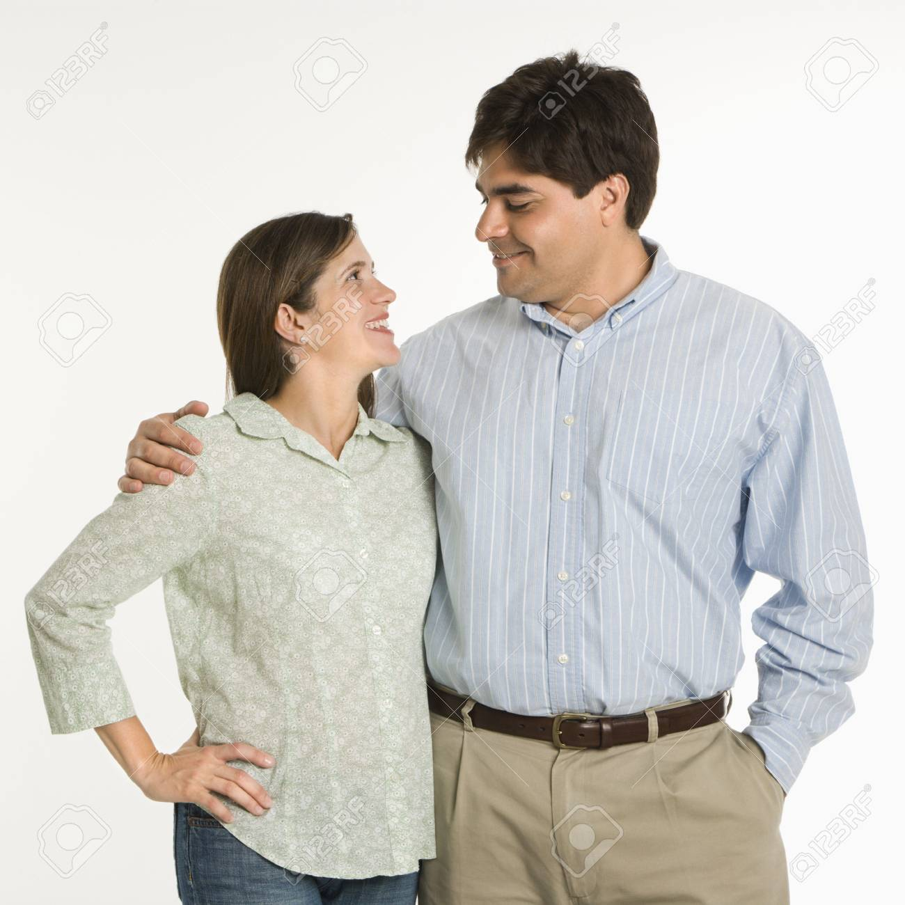 Couple standing smiling at eachother against white background. Stock Photo - 1874590