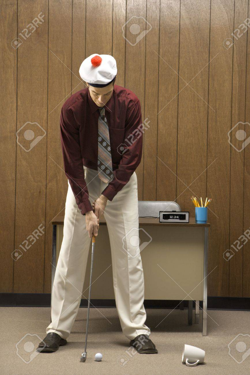 Caucasion mid-adult retro businessman wearing cap putting golf ball into coffee cup in his office. Stock Photo - 1991622