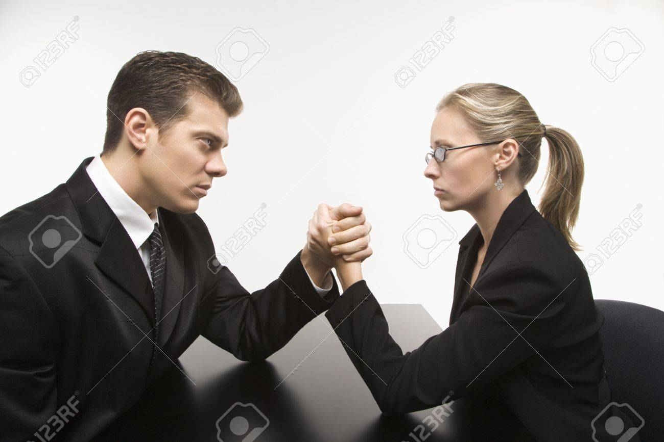 Side view of Caucasian mid-adult businessman and businesswoman arm wrestling on table. Stock Photo - 1991659