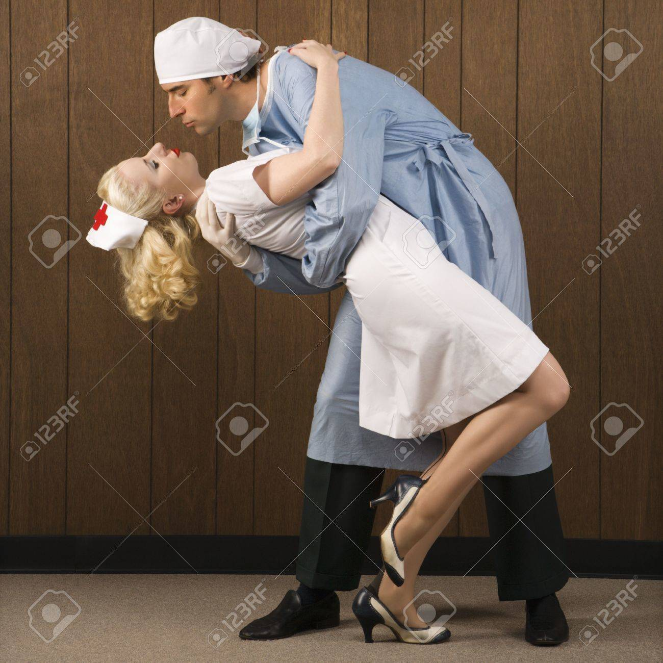 Mid-adult Caucasian male surgeon bending female nurse over backwards for passionate embrace. Stock Photo - 2029321