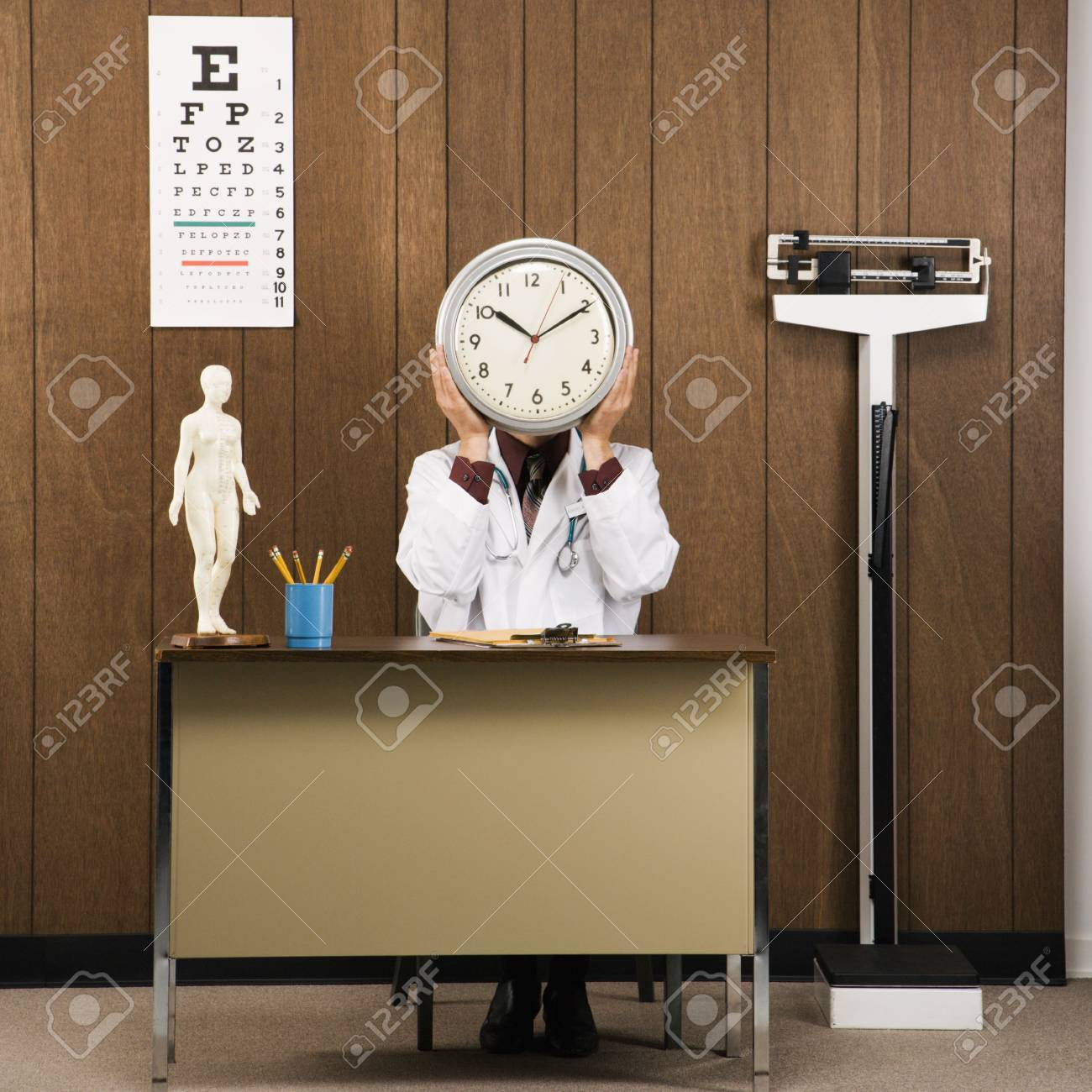 Caucasian male doctor sitting at desk holding clock over face. Stock Photo - 1934101