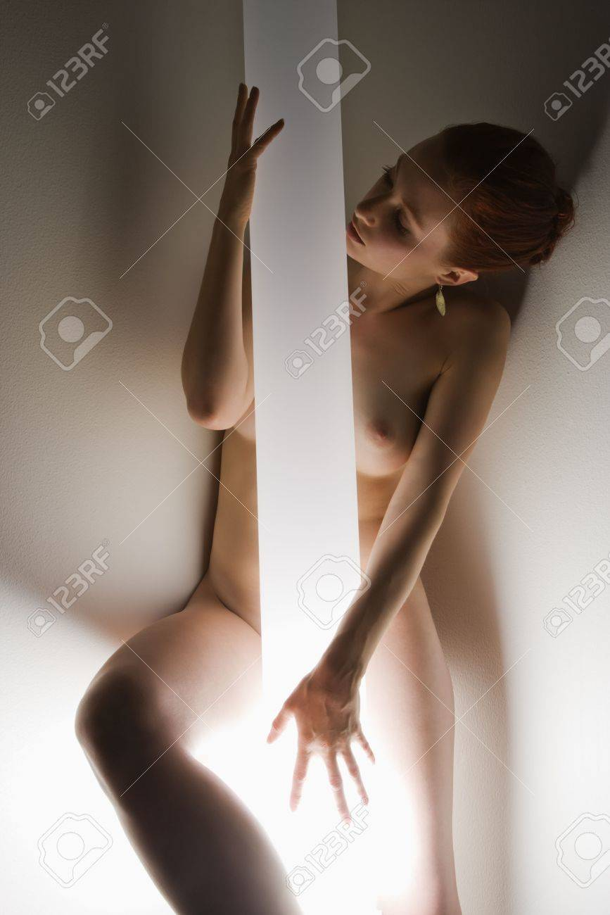 Nude Caucasian woman standing with body wrapped around light pole. Stock Photo - 2044249