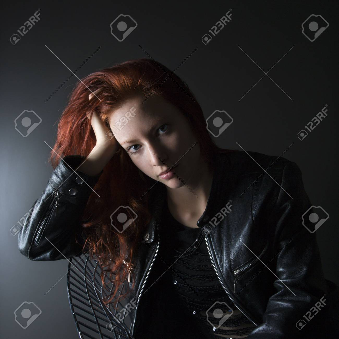 Portrait of pretty redhead young woman sitting in chair resting head on hand. Stock Photo - 2044387