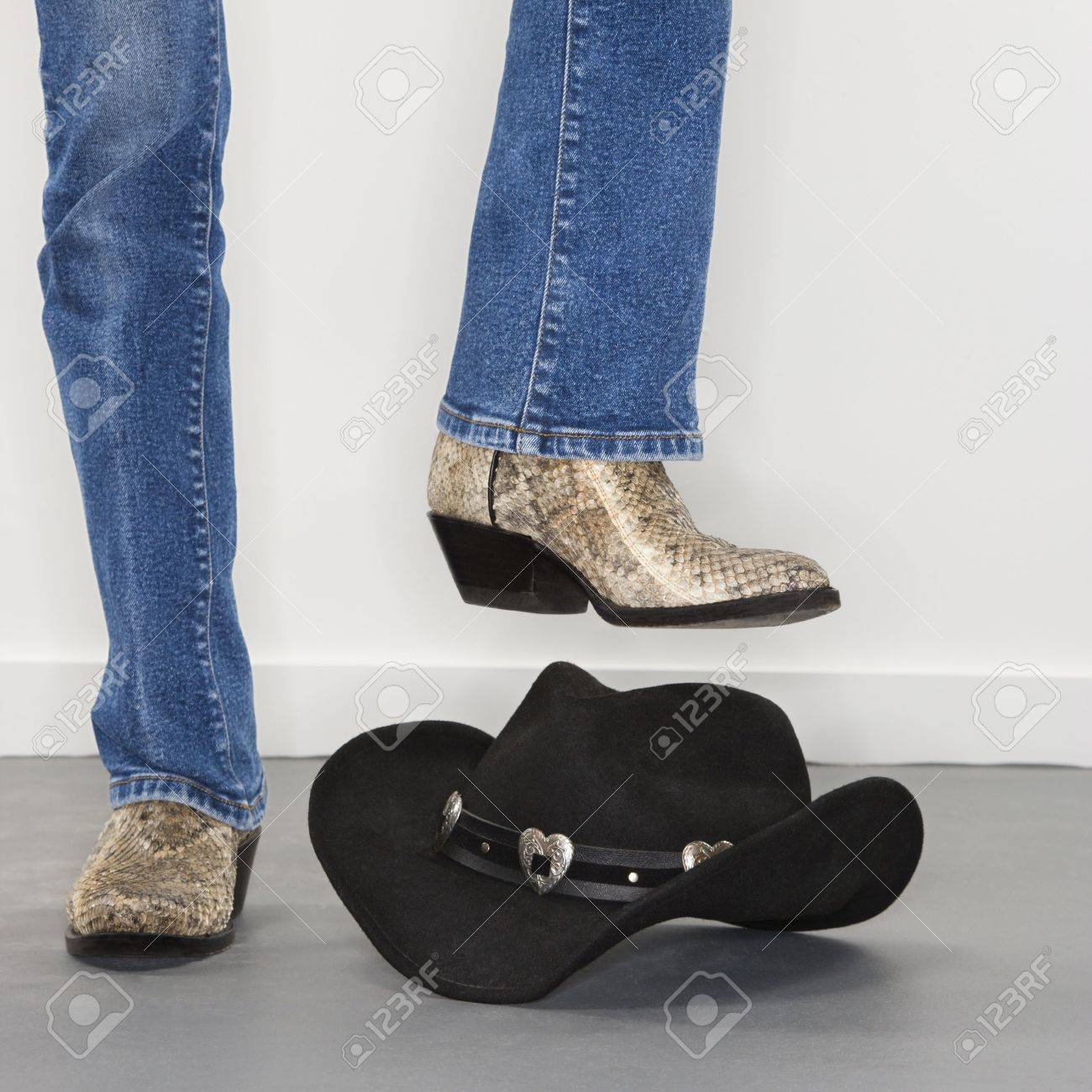 a3e14779ad0 Woman wearing snakeskin cowboy boots holding foot as if to stomp..