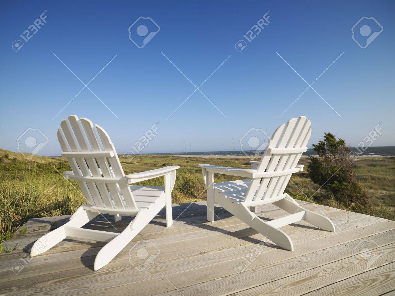 Two Adirondack Chairs On Wooden Deck Overlooking Beach At Bald