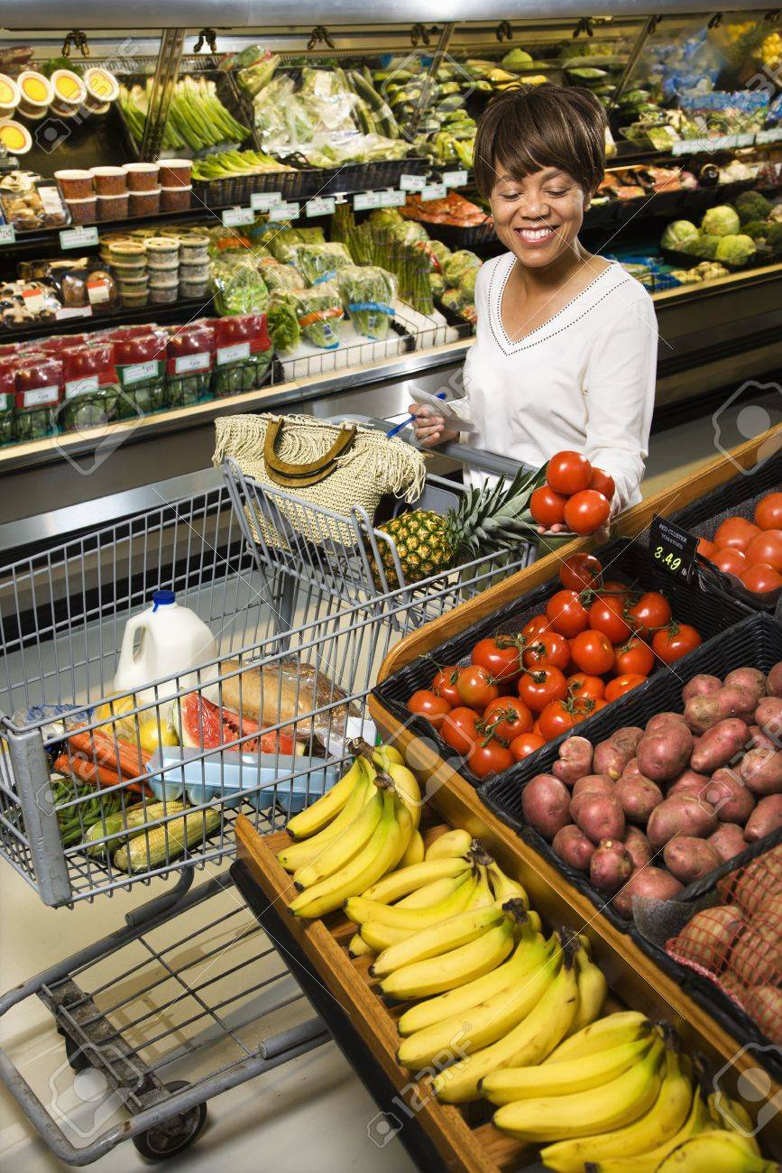 Smiling middle aged African American woman selecting tomatoes from grocery store produce. Stock Photo - 2044470