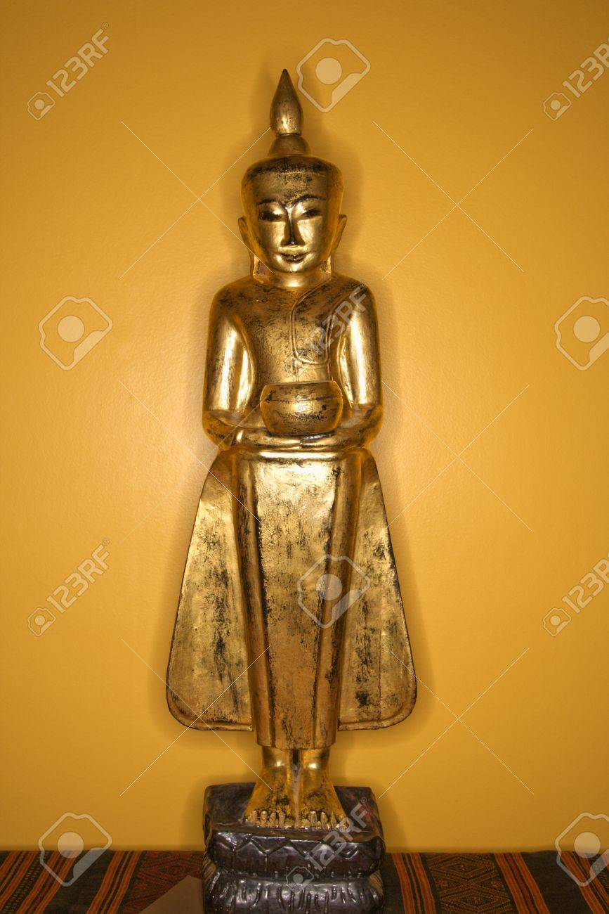 Golden Wooden Buddha Statue From Myanmar Against Yellow Wall. Stock ...