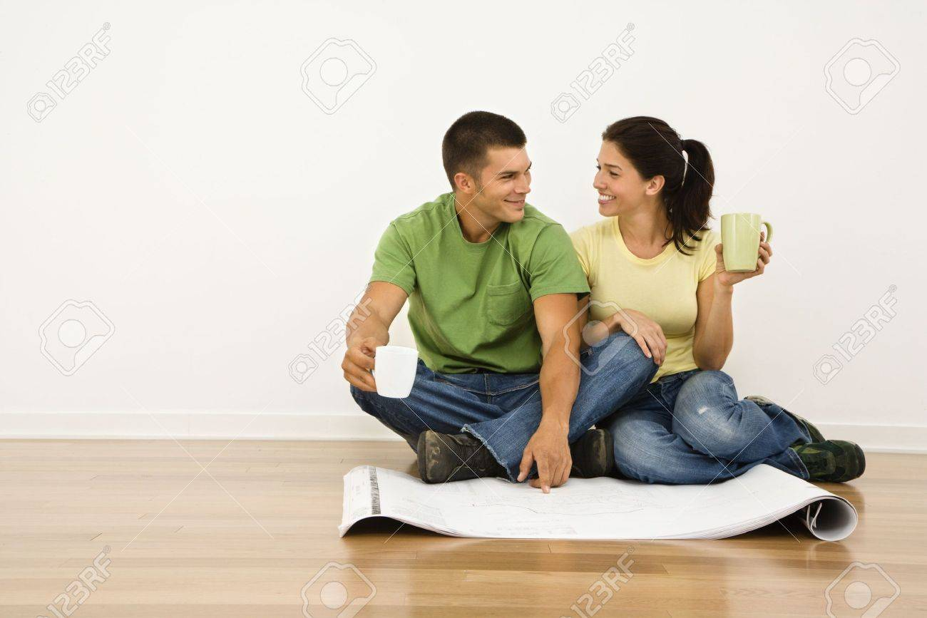 ttractive ouple Sitting On Home Floor With offee ups Looking ... - ^