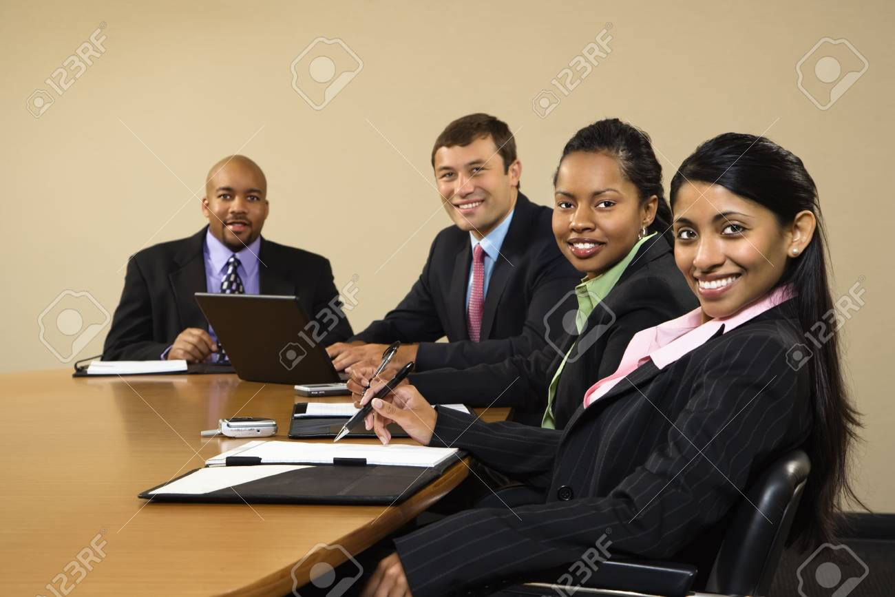 Businesspeople sitting at conference table smiling. Stock Photo - 2115164