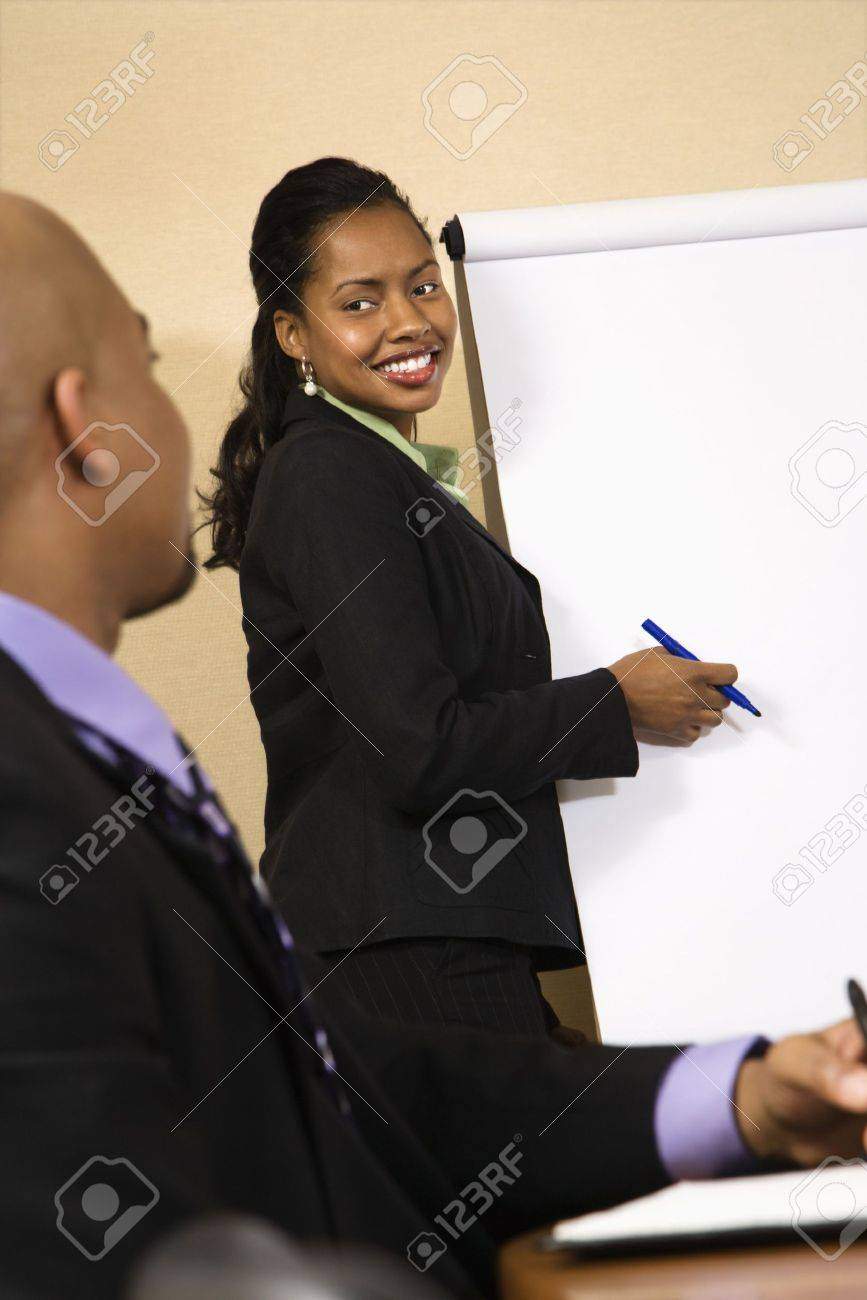 Businesspeople sitting at conference table  while businesswoman gives presentation. Stock Photo - 2115156