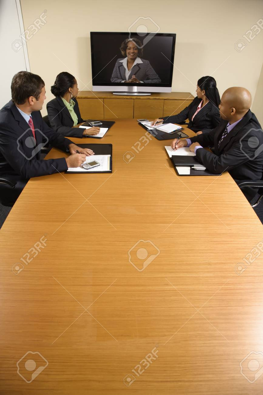 Businesspeople sitting at conference table looking at flat screen display. Stock Photo - 2115237