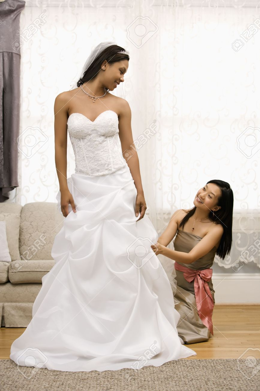Asian Bridesmaid Fixing African-American Bride\'s Dress. Stock Photo ...