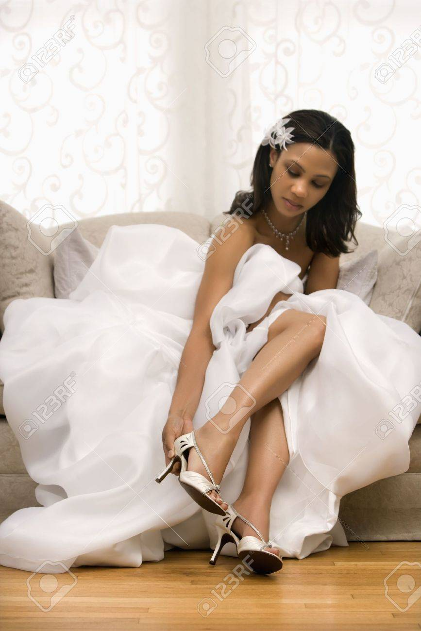 African-American bride placing shoe on foot. Stock Photo - 2145710