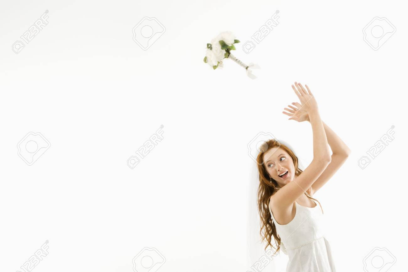 Portrait of Caucasian bride tossing bouquet behind her. Stock Photo - 2147355