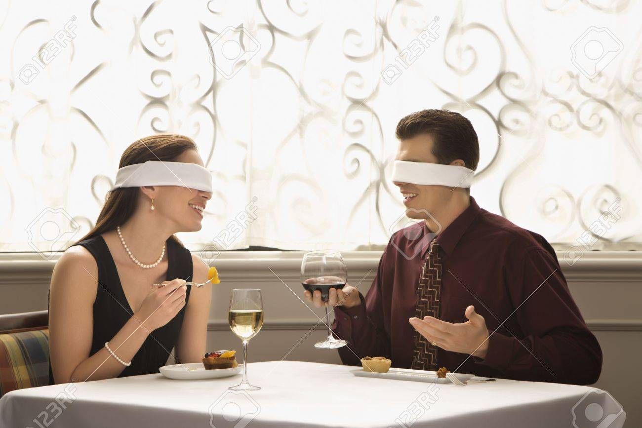 Mid adult Caucasian couple dining in a restaurant with blindfolds over eyes. Stock Photo - 2190840