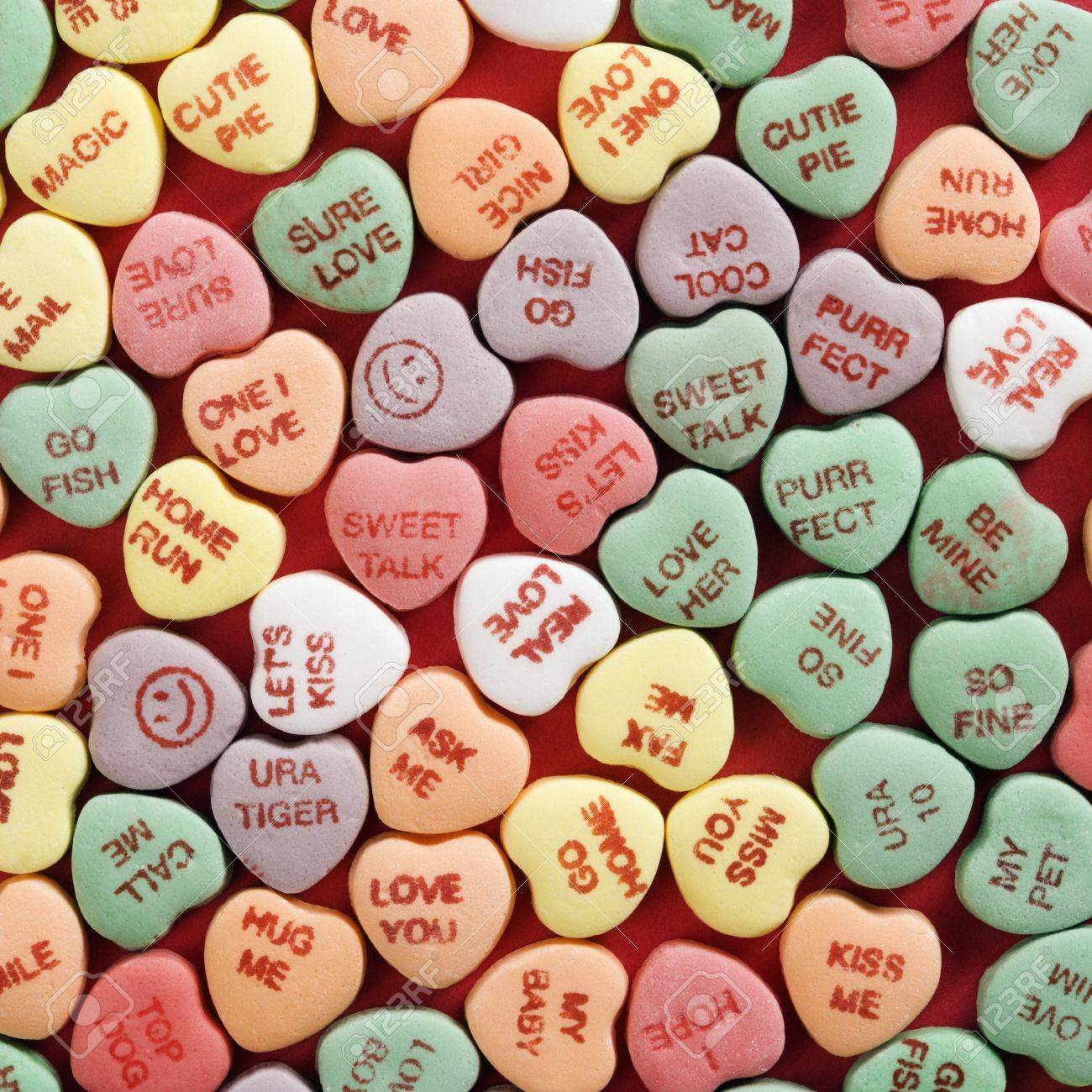 Large group of colorful candy hearts with sayings on them arranged on red background. Stock Photo - 2190098