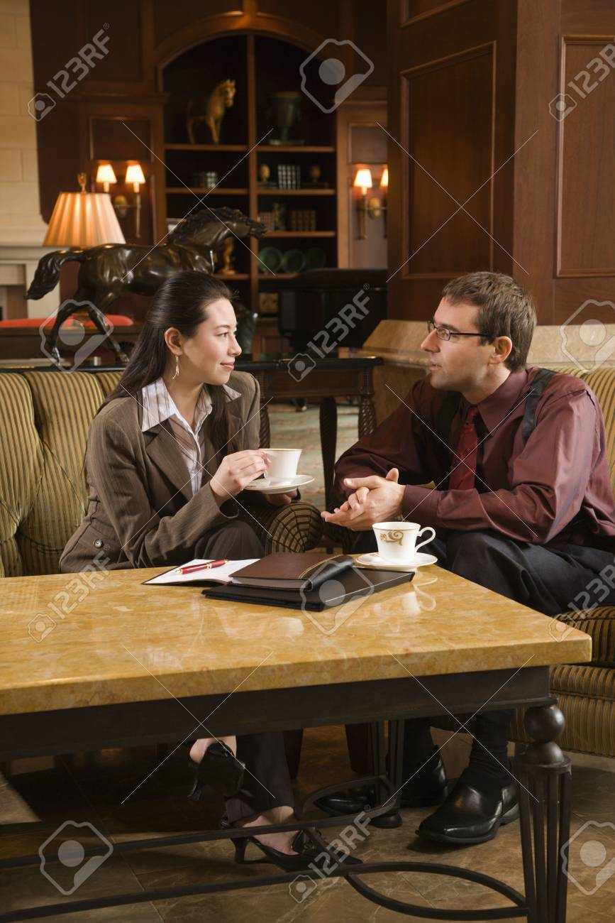 Caucasian mid adult businessman and woman drinking coffee and conversing. Stock Photo - 2176044