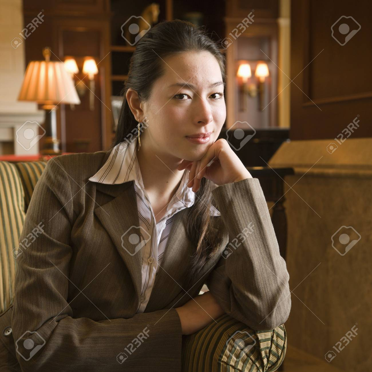 Taiwanese mid adult buisinesswoman looking at viewer with head resting on hand. Stock Photo - 2176109