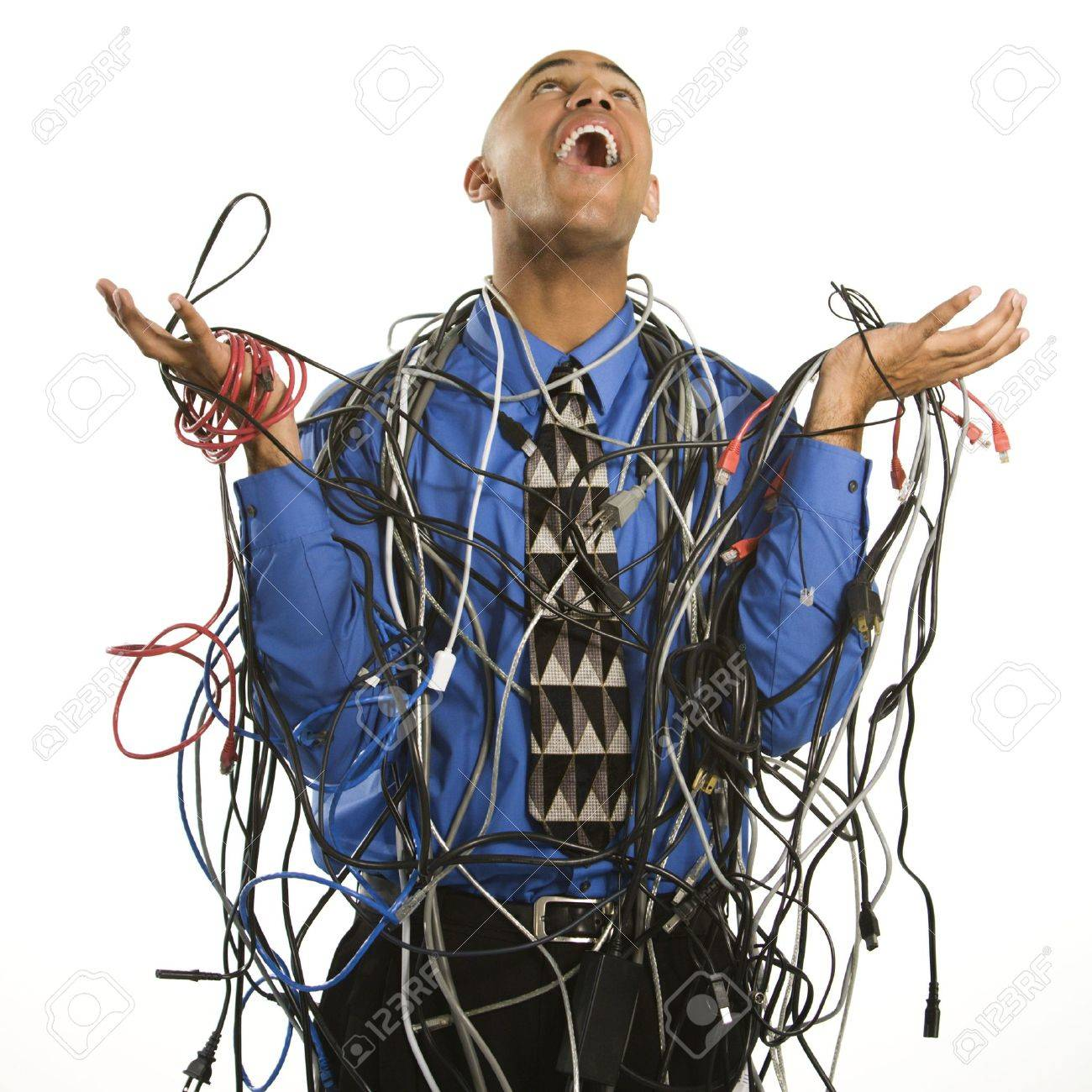 African American businessman wrapped in computer cables looking up with exasperation. Stock Photo - 2176152