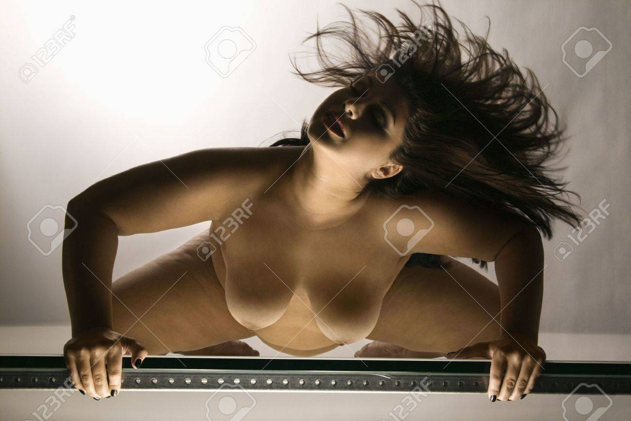 young adult caucasian female nude flinging hair. stock photo