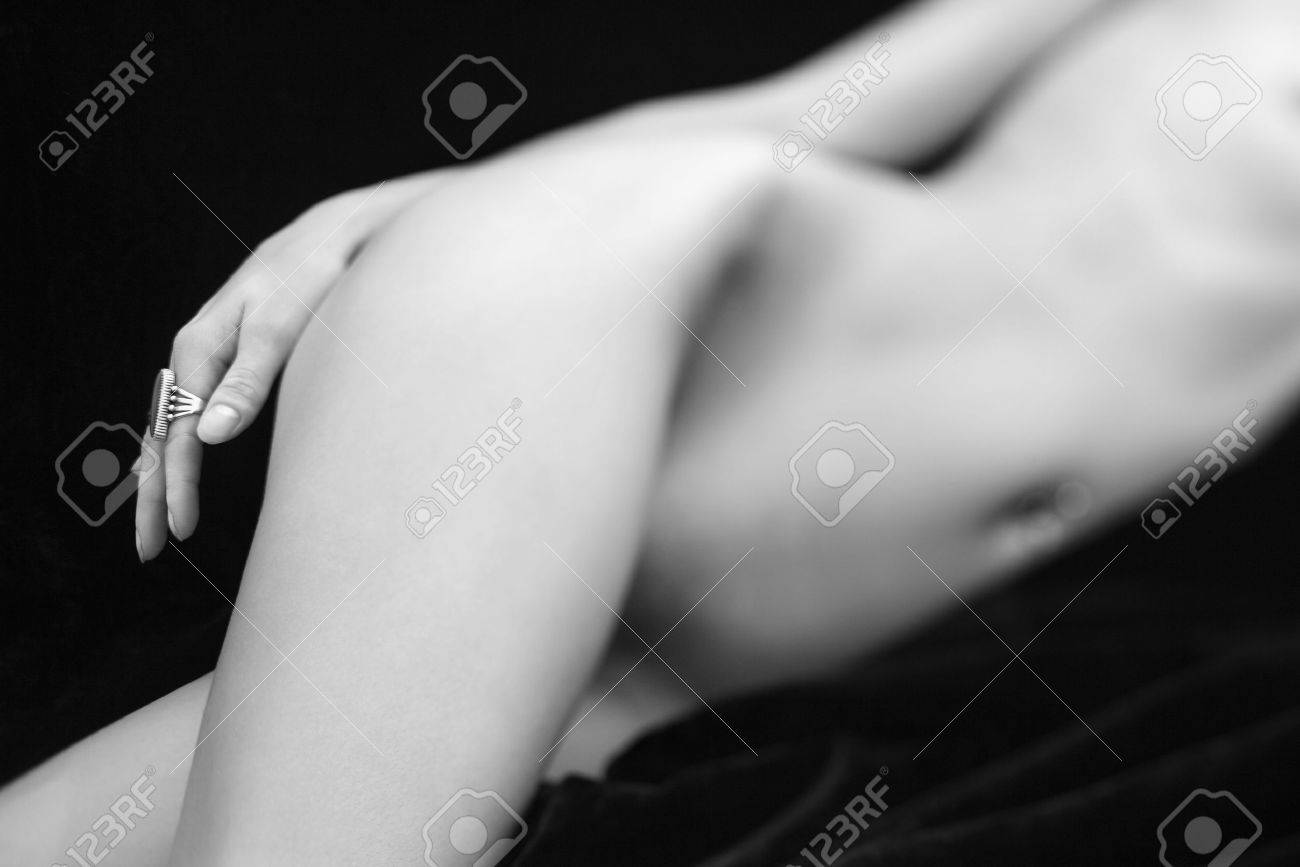 selective focus of caucasian mid adult female nude body lying