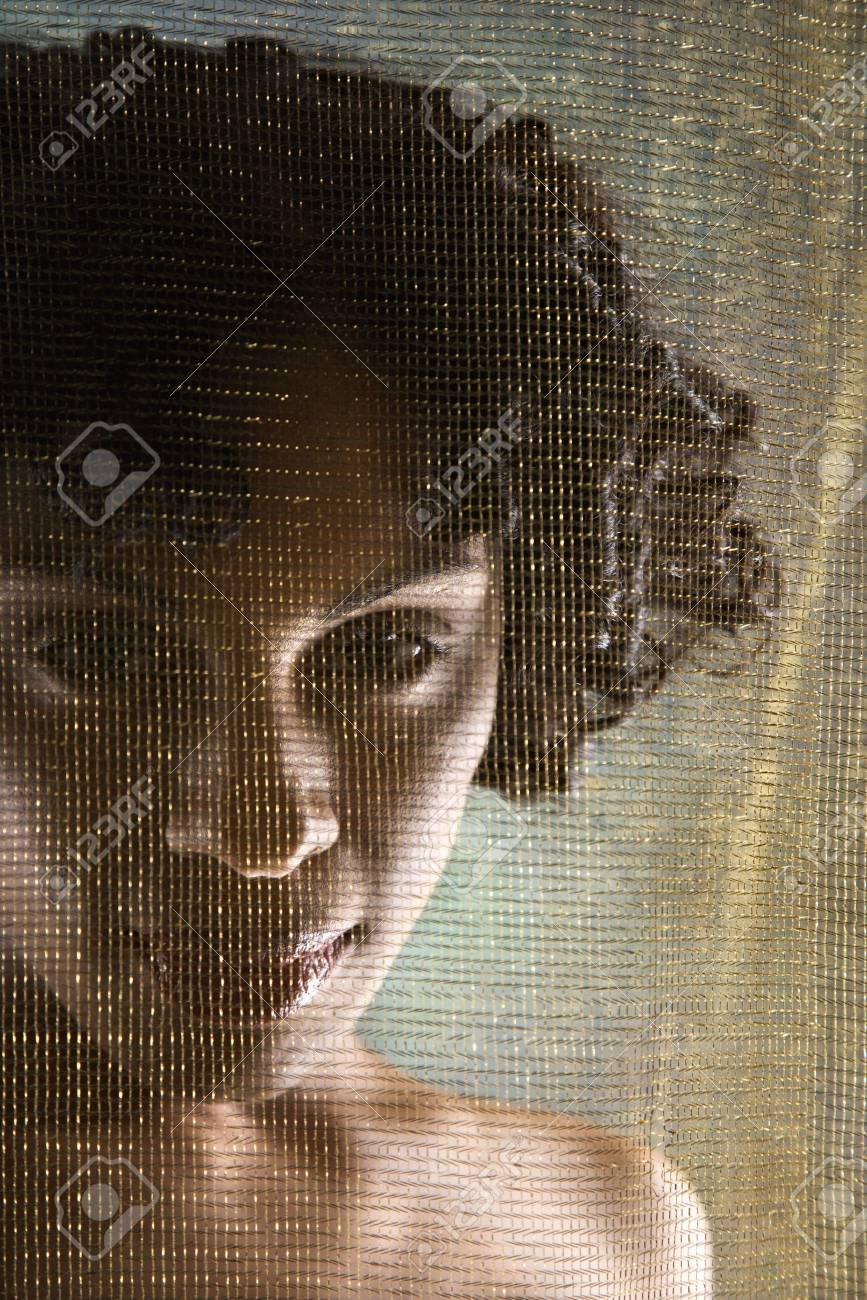 Hispanic woman looking at viewer from behind sheer fabric. Stock Photo - 2189646