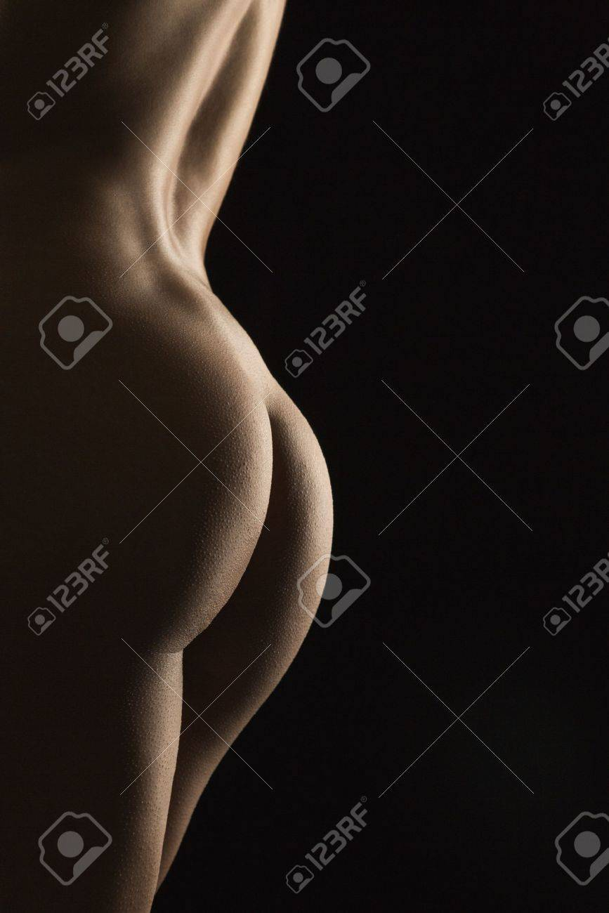 side view of nude hispanic mid adult female back and buttocks. stock