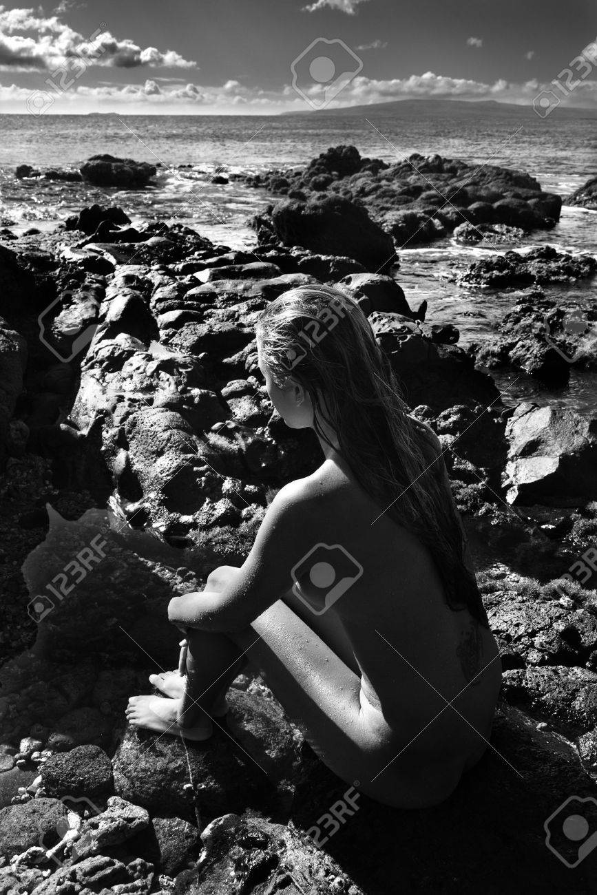 Rear view of Filipino young nude woman sitting on rocky beach. Stock Photo - 2189559