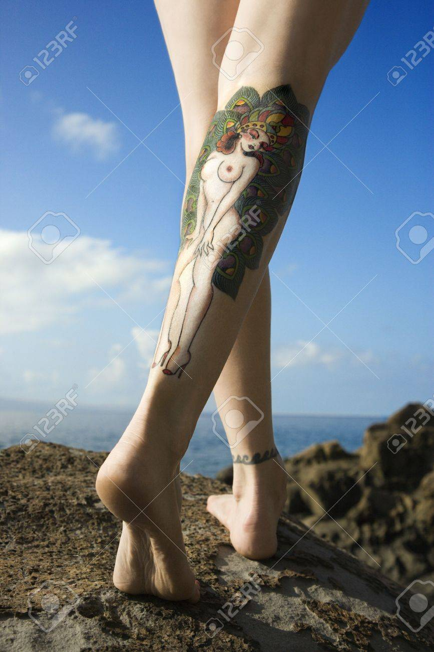 Back view of Caucasian woman's legs covered with sexy tattoo. Stock Photo - 2189839