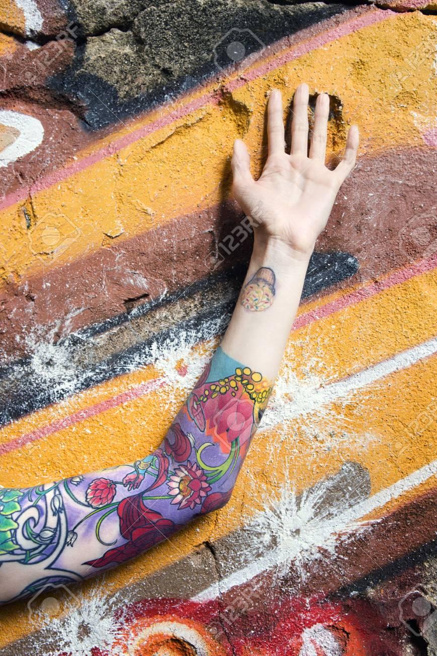 Tattooed Caucasian woman's arm against graffiti covered wall. Stock Photo - 2168725