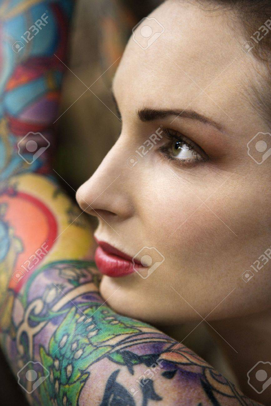 Close-up of attractive Caucasian woman's face and tattooed arm. Stock Photo - 2189838