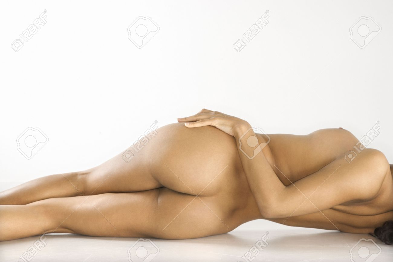 Back view of attractive nude woman lying on floor against white background. Stock Photo - 2204704