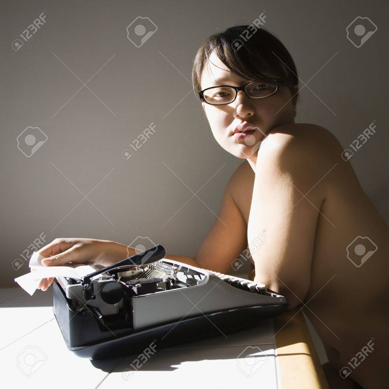 Pretty  young Asian woman sitting at kitchen table with typewriter. Stock Photo - 2205265