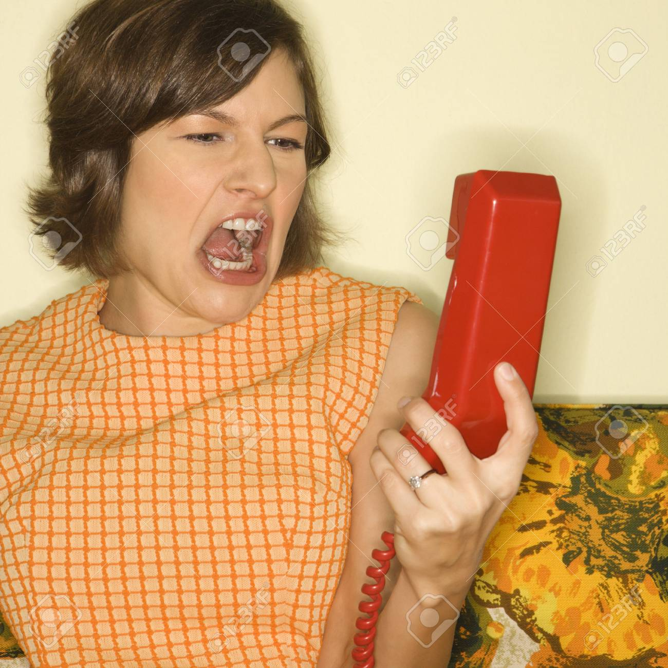 Pretty Caucasian mid-adult woman screaming at red telephone receiver. Stock Photo - 2205787