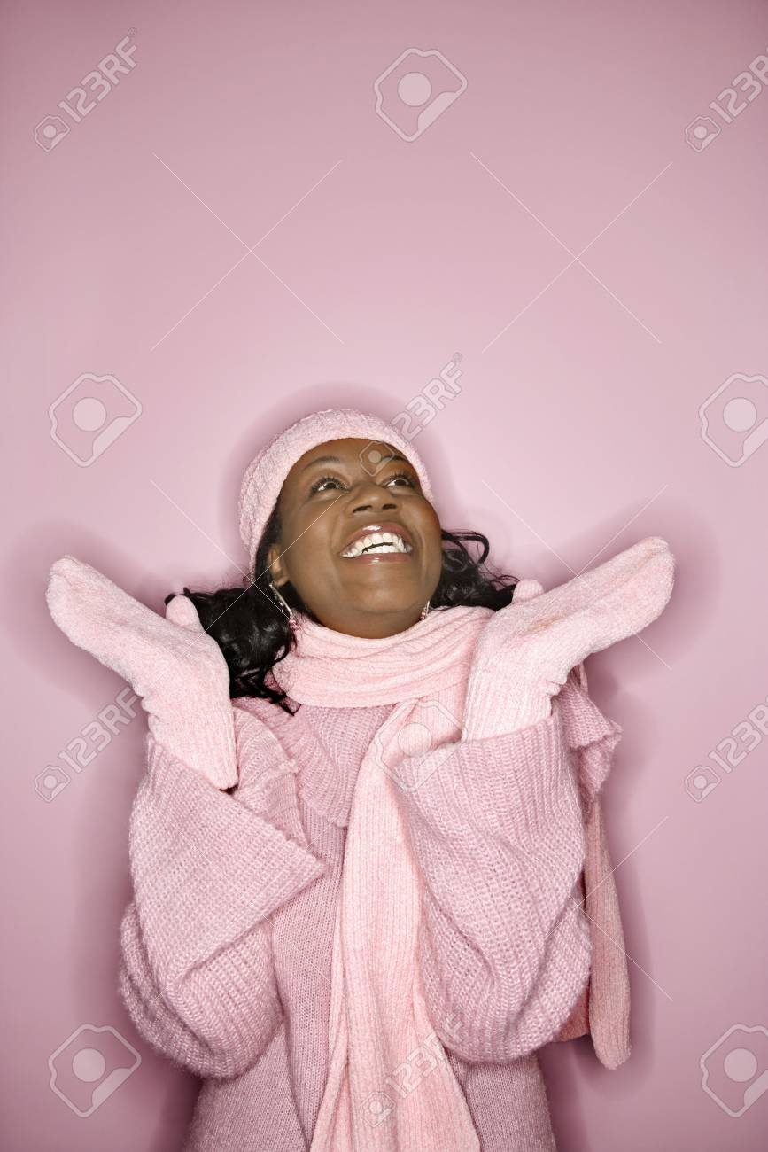 Portrait of smiling African-American mid-adult woman on pink background wearing  winter coat 51e6a856863e