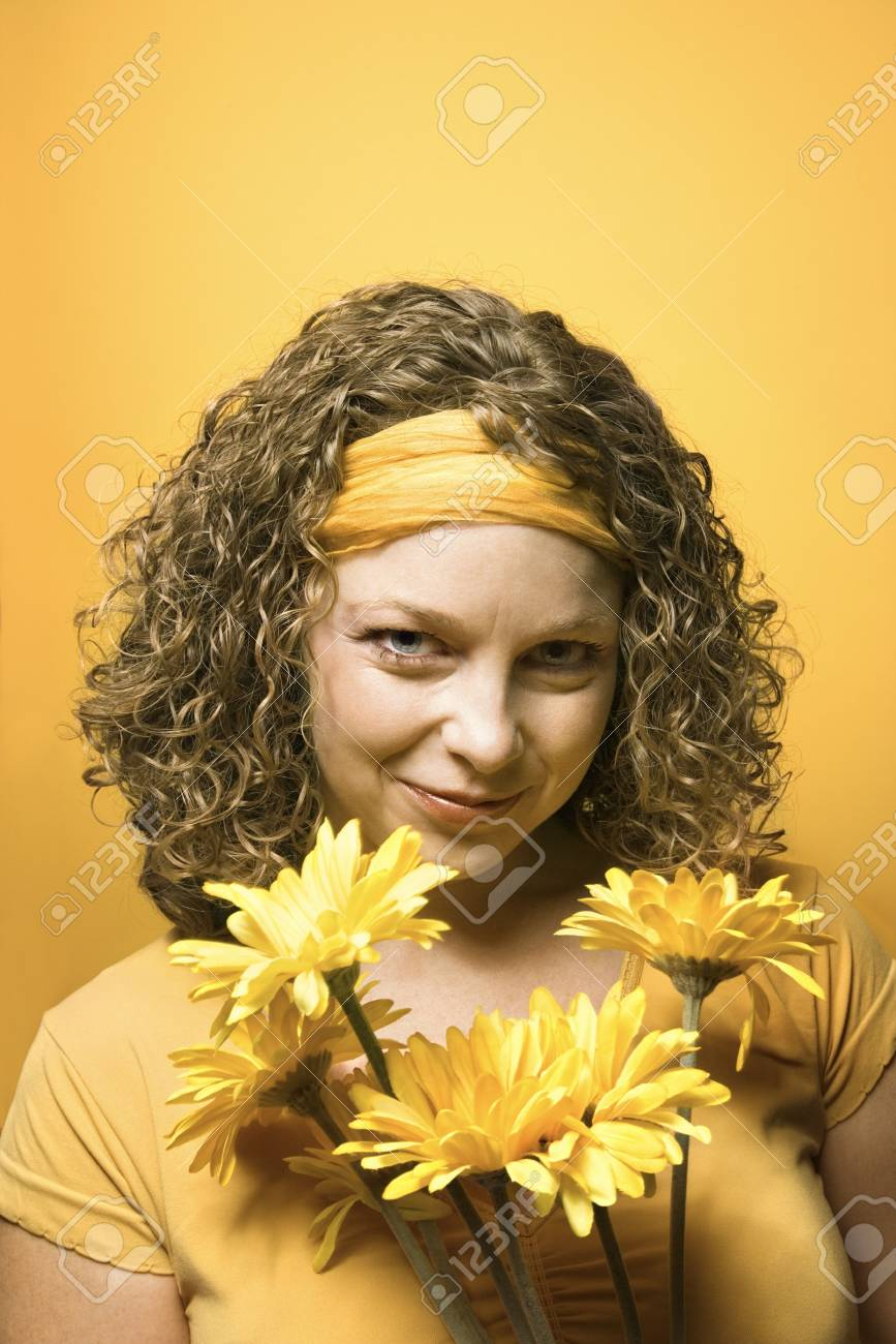 Portrait of young adult Caucasian woman on yellow background holding bouquet of flowers. Stock Photo - 2219742