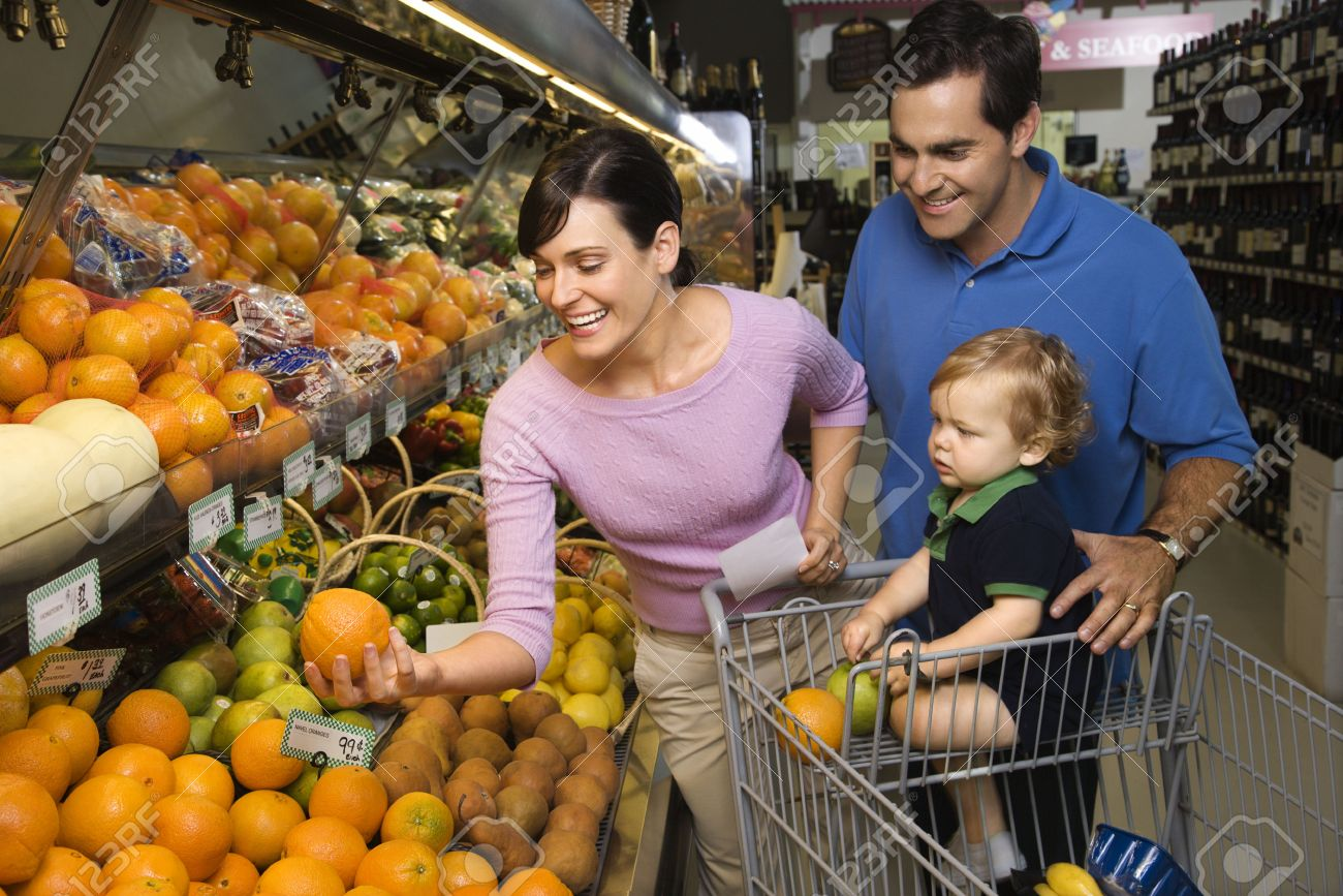 Caucasian mid-adult parents grocery shopping for fruit with male toddler. Stock Photo - 2456770