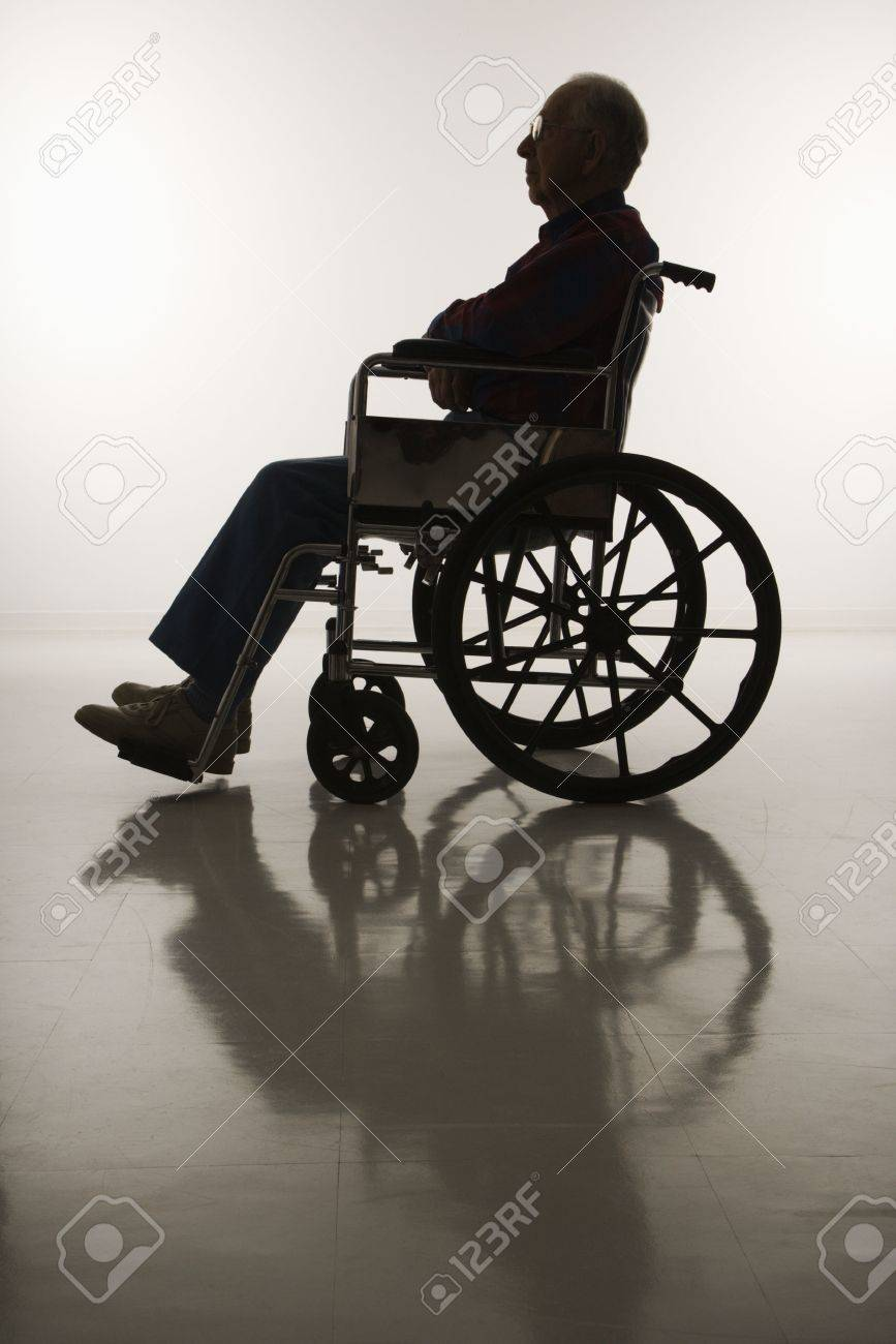 Profile view of silhouetted Caucasion elderly man sitting in wheelchair. Stock Photo - 2245964
